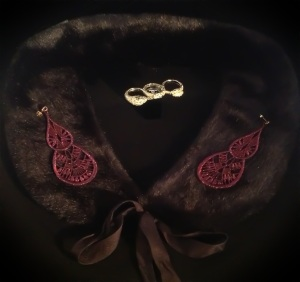 Large sparkly granate tear drop Venetian lace earrings with gold hardware here with black Prada faux-fur collar and gold serpent 3 finger ring